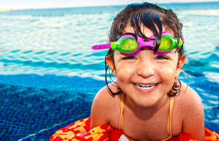 A beautiful happy little girl smiling with pink and green googles and colorful life vest in infinity pool