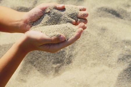Photo pour Close up onChilds hands holding sand.summer beach holiday vacation concept - image libre de droit