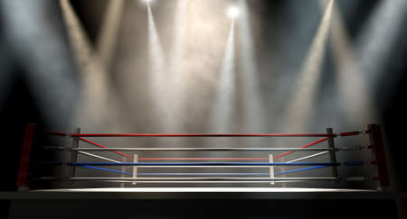 A regular boxing ring surrounded by ropes spotlit by various lights on an isolated dark background