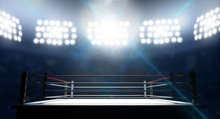 An boxing ring surrounded by ropes spotlit by floodlights in an arena setting at night
