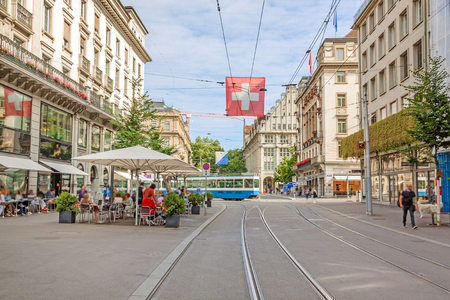 Photo for Shopping promenade called Bahnhofstrasse, inner city of Zurich. Cafe with people sitting in front, tram / train in background, with swiss flag. - Royalty Free Image