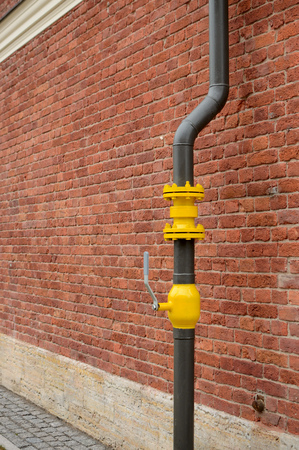 Photo pour Along the wall there is a gas pipe.On the pipe the valve is installed. - image libre de droit