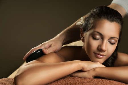 Photo for Beautiful girl has hot stone massage. Spa treatment. - Royalty Free Image