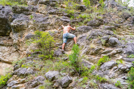 Photo for Young man climber in jeans shirts and bare torso climbs on rocks to the top in mountains of Altai without equipment and insurance - Royalty Free Image