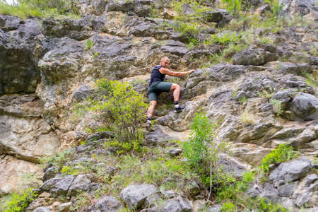 Photo for Young boy climber in sports clothes climbs on rocks to the top in mountains of Altai without equipment and insurance - Royalty Free Image