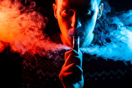 Foto per Portrait of a guy with a shadow on a serious face  with a colored backlight of blue and red smoking a vape and exhaling multi-colored smoke in different directions on a black isolated background - Immagine Royalty Free