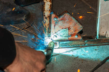 Foto de An experienced person performs work with a welding machine, fixing metal parts, removing blue smoke and yellow sparks and lightning in the industrial production workshop. - Imagen libre de derechos