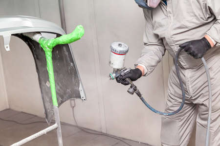 Photo pour A male worker paints with a spray gun a part of the car body in silver after being damaged at an accident. Bumper from the vehicle during the repair in the workshop. - image libre de droit