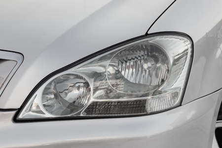 Foto de Front headlamp view of silver used car stands in the auto showroom sale after washing and polish with orange turn light and halogen lamp. Auto service industry. - Imagen libre de derechos