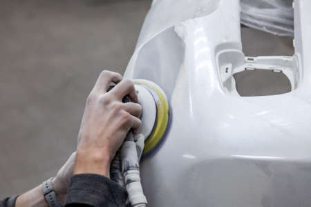 Foto de Preparation for painting a car element using sander and putty by a service technician leveling out before applying a primer after damage to a part of the body in an accident in the vehicle workshop - Imagen libre de derechos
