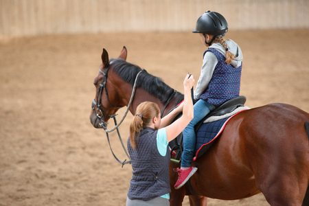 Foto de Girl in helmet Learning Horseback Riding. Instructor teaches teen Equestrian. - Imagen libre de derechos