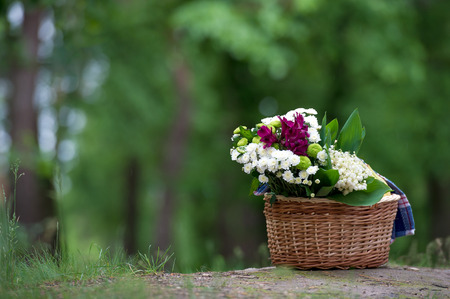 Photo pour A magnificent bouquet of lilies of the valley and other flowers in a wooden basket in the background of the forest - image libre de droit