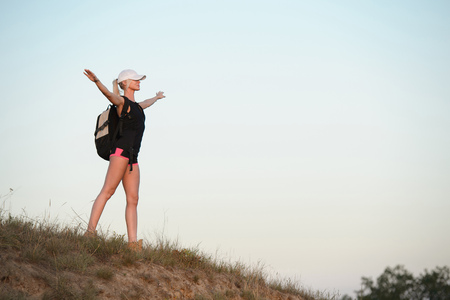 Photo pour Woman with hands up standing on the top of the hill. Travel, vacation, holidays and adventure concept. - image libre de droit