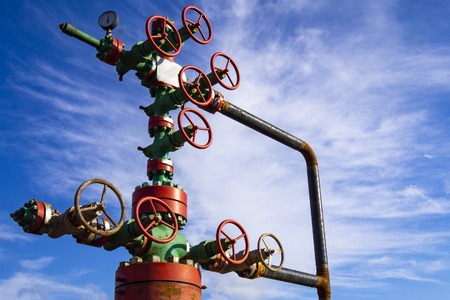 Photo pour Horizontal view of a wellhead with valve armature. Oil and gas industry concept. Industrial site background. Toned. - image libre de droit