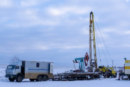 Photo pour Wireline equipment hanging from top drive ready to be lowered downhole for logging. An oil well engineer works from the back of specialised van to log the condition of steel casing inside an oil well. - image libre de droit