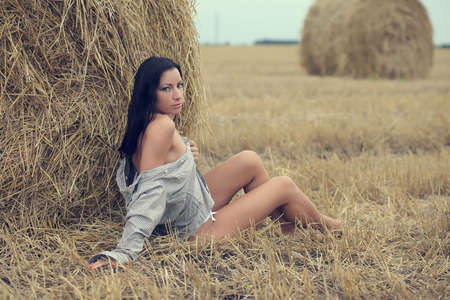 beautiful woman sitting in field with haystacks