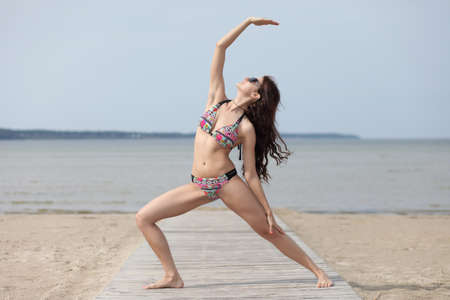 Photo for beautiful girl with sexy body meditating on a beach - Royalty Free Image