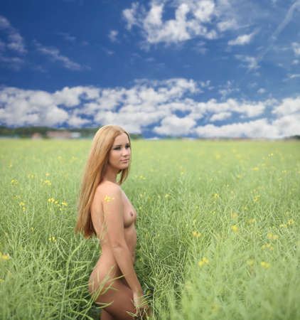 Photo for Young naked sexy girl walking in the field - Royalty Free Image
