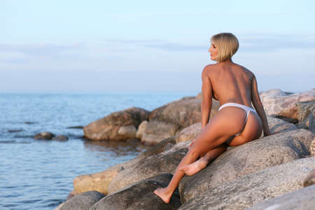 Photo pour young naked athletic girl on the stone by the sea - image libre de droit