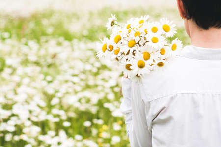 Photo pour The woman in white clothes with a bouquet in her hand in the field of camomiles - image libre de droit