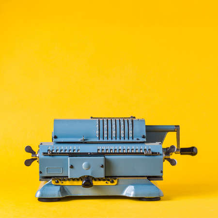 Foto de Old calculating machine on yellow background. Accounting or business concept - Imagen libre de derechos