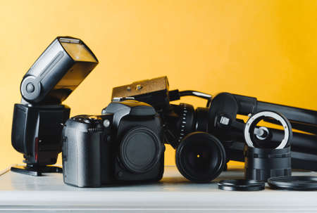 Foto de Digital camera, lenses and equipment of the photographer on a yellow background - Imagen libre de derechos