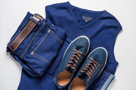 Foto de Fashionable men's clothing. Jeans and shoes on light background - Imagen libre de derechos