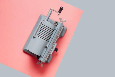 Foto de Old counting machine on a pale pink background - Imagen libre de derechos