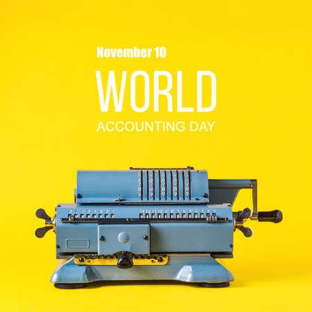 Foto de Old calculating machine on yellow background. Word Accounting day  concept - Imagen libre de derechos