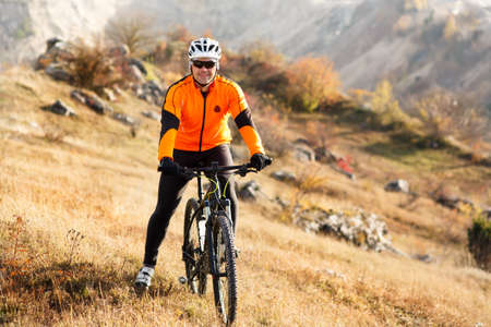 Man in helmet and glasses stay on the bicycle under landscape with rocks and hill.