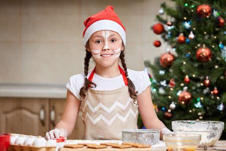 Foto de Little girl baking Christmas cookies at home - Imagen libre de derechos
