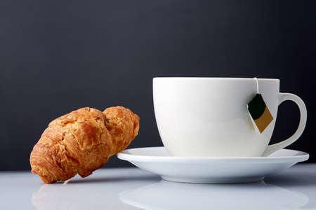 Foto de Breakfast with te and croissants on grey background, close-up - Imagen libre de derechos