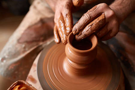 Photo pour Close-up hands of a male potter in apron making a vase from clay, selective focus - image libre de droit