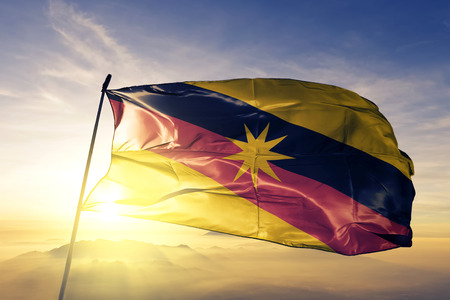 Photo pour Sarawak state of Malaysia flag textile cloth fabric waving on the top sunrise mist fog - image libre de droit