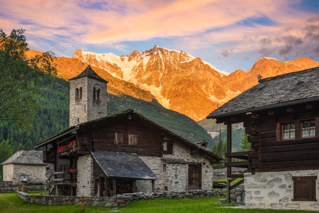 Foto de Spectacular east wall of Monte Rosa at dawn from the picturesque and characteristic alpine village of Macugnaga (Staffa - Dorf) with old-fashioned houses and the old church, Italy - Imagen libre de derechos
