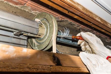 Foto de Rolling shutter repair. Worker adjusts a broken roller shutter of a home. Close-up of hands with gloves and orange starter screwdriver - Imagen libre de derechos