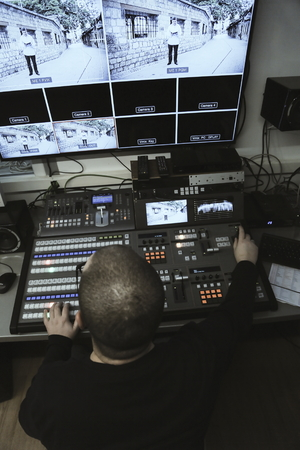Photo for TV editor working with audio video mixer in a television broadcast studio desk station - Royalty Free Image