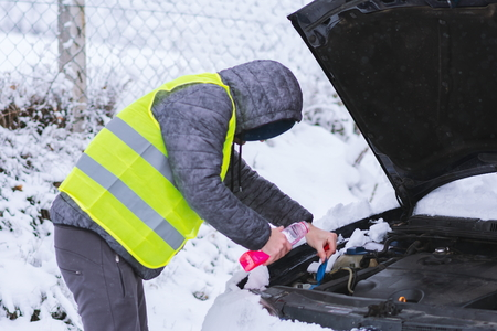 Photo pour Man dressed in neon green vest pouring antifreeze coolant to car engine at cold winter day. - image libre de droit