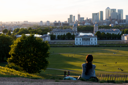Foto de Woman sitting on the ground on the top of the hill at Greenwich Park, London and watching the sunset - Imagen libre de derechos