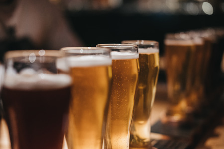 Photo for Close up of a rack of different kinds of beers, dark to light, on a table. Selective focus. - Royalty Free Image