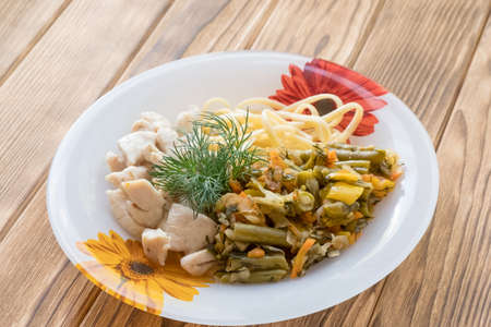 Foto de Chicken meat in a plate with fried vegetables and pasta - Imagen libre de derechos