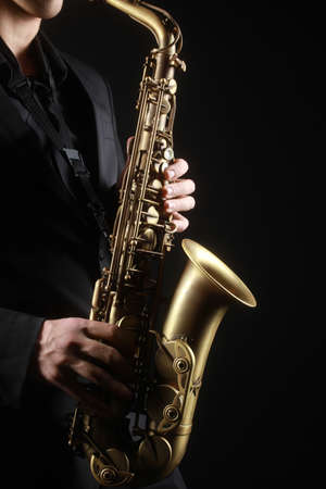 Photo for Saxophone classical music instruments Saxophonist with alto sax closeup on black - Royalty Free Image