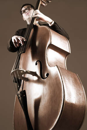 Photo pour Double bass player contrabass playing. Classical musician jazz bassist. Focus is on the strings - image libre de droit