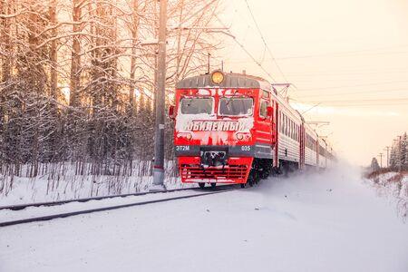Foto per Russian train in the winter. The train rides by rail in the winter in the woods. Winter forest. Public transport. Russia Leningrad region, Gatchina district January 6, 2019 - Immagine Royalty Free