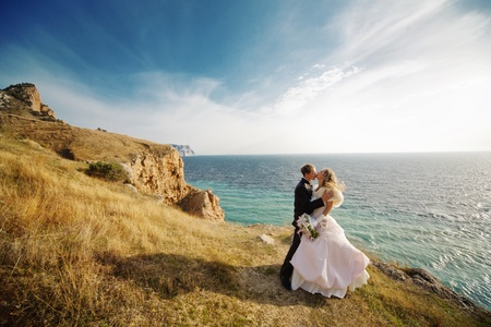 Foto de Kissing wedding couple staying over beautiful landscape - Imagen libre de derechos