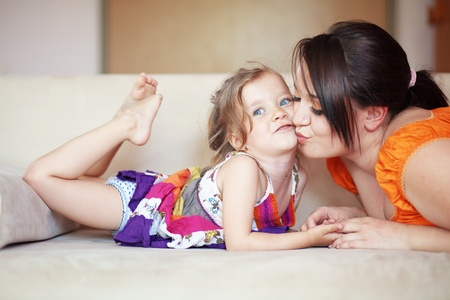 Photo for Mother with her small daughter playing on the sofa at home - Royalty Free Image