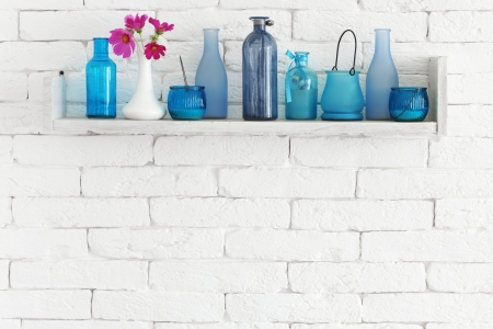 Photo for Decorative shelf on white brick wall with blue bottles on it - Royalty Free Image