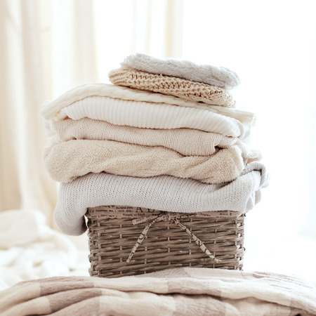 Photo pour Stack of cozy knitted sweaters in wicker backet - image libre de droit