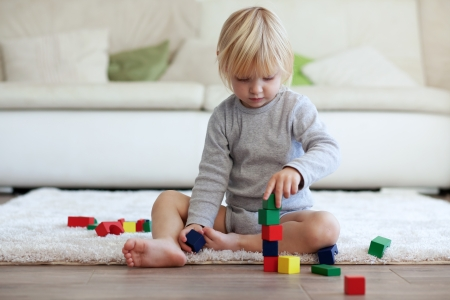 Photo pour Toddler playing with wooden blocks at home - image libre de droit