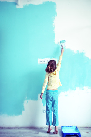Foto de 7 years old girl painting the wall at home, style toning - Imagen libre de derechos
